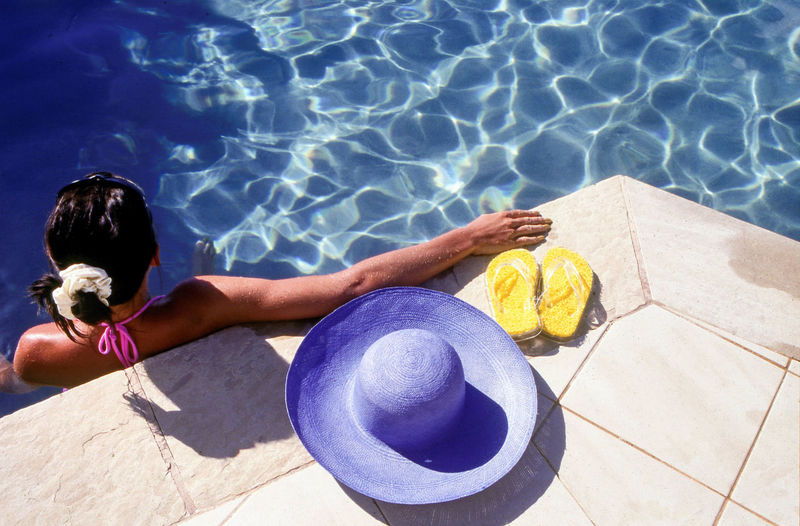 High Angle View Of Woman With Hat And Slippers Relaxing In Swimming Pool