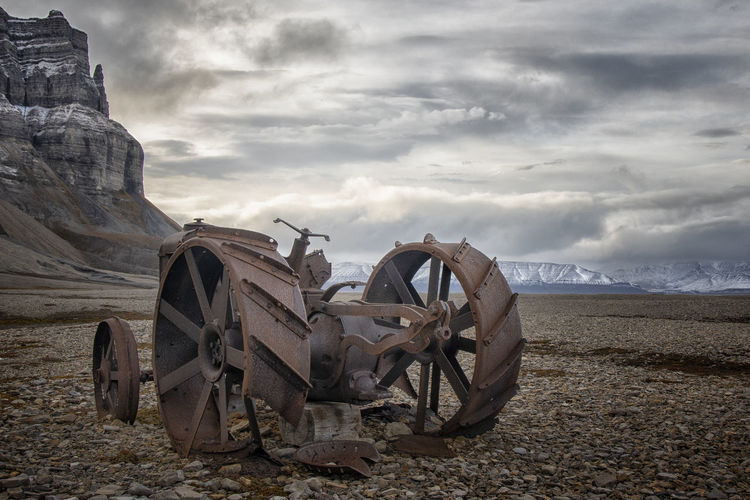 Old abandoned truck on field against sky