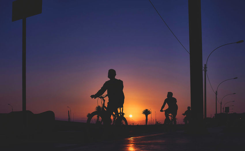 Silhouette people standing on street against sky during sunset
