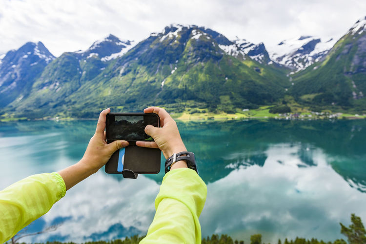Man photographing using smart phone against mountains