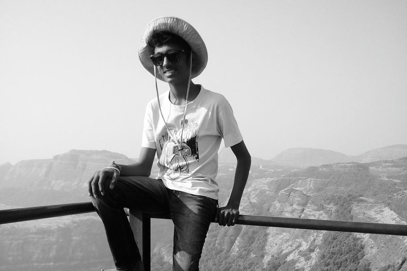 Happy young man wearing sunglasses and hat leaning on railing against sky