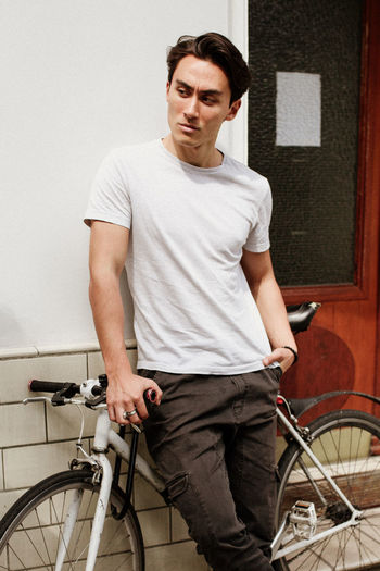 Portrait of young man standing on bicycle