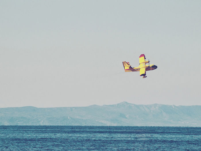 Firefighting Aircraft Flying Over Sea Against Clear Sky