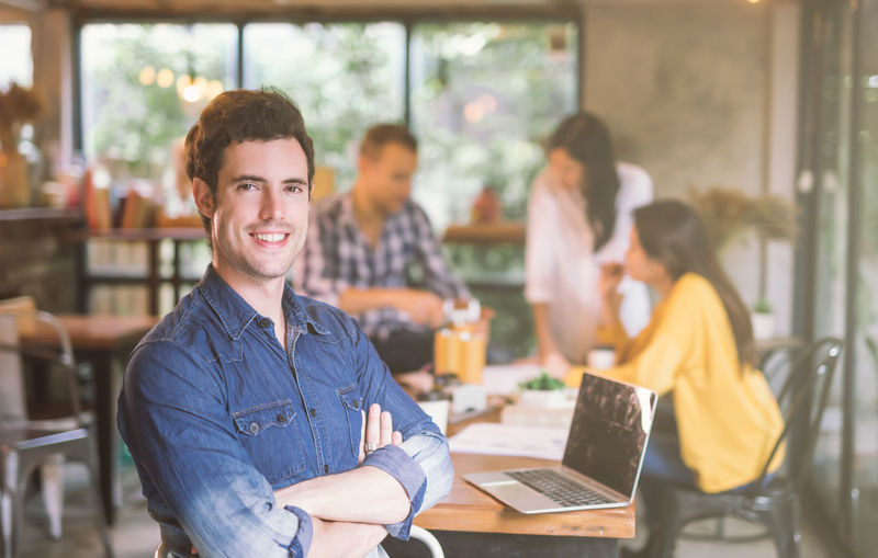 Portrait of businessman smiling while working with coworkers in cafe