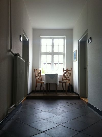 Empty chairs and table in corridor