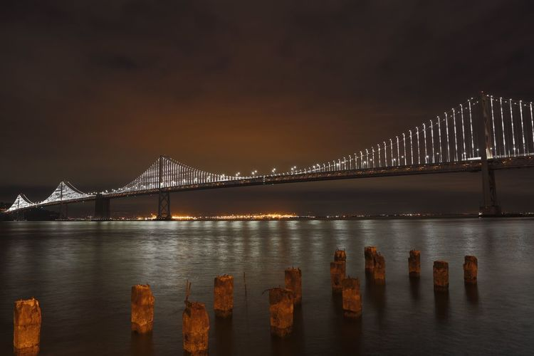 View of bay bridge illuminated at night