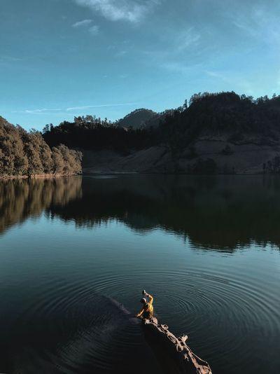 Man Sitting On Log In Lake Against Trees