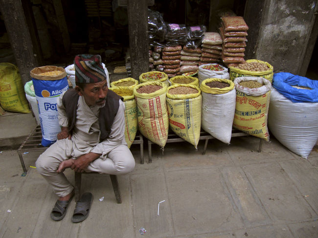 A grain vendor waits for customers in the Ason Bazaar in Kathmandu Nepal. Business Cultures Day Full Length Headwear Kathmandu Male Man Market Market Stall Men Nepal Nepali  Occupation One Man Only One Person People Sales Occupation Selling Senior Adult Sitting Trader Tradition Traditional Clothing