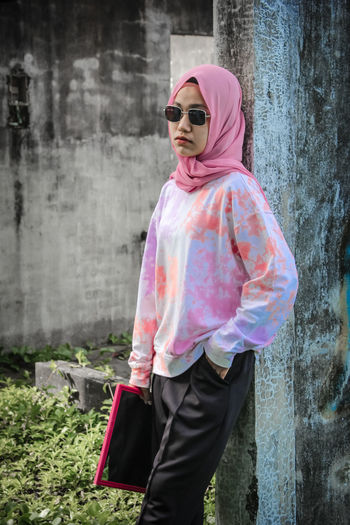 Young woman wearing sunglasses standing against pink wall