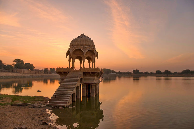 Sunrise over stone tower and historical building in Gadi Sagar lake, Jaisalmer, India. Architecture Building Exterior Built Structure Cloud - Sky Gadisagar Temple Gadisarlake History Jaisalmer Lake Nature No People Orange Color Reflection Religion Scenics - Nature Sky Sunset The Past Travel Travel Destinations Water Waterfront