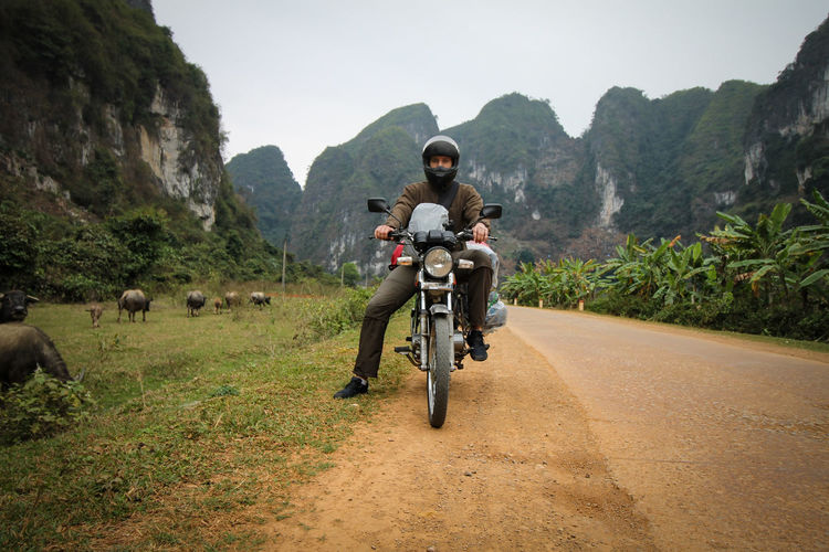 Full length of man riding motorcycle on road against mountains
