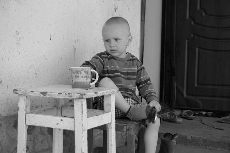Boy sitting at table against wall