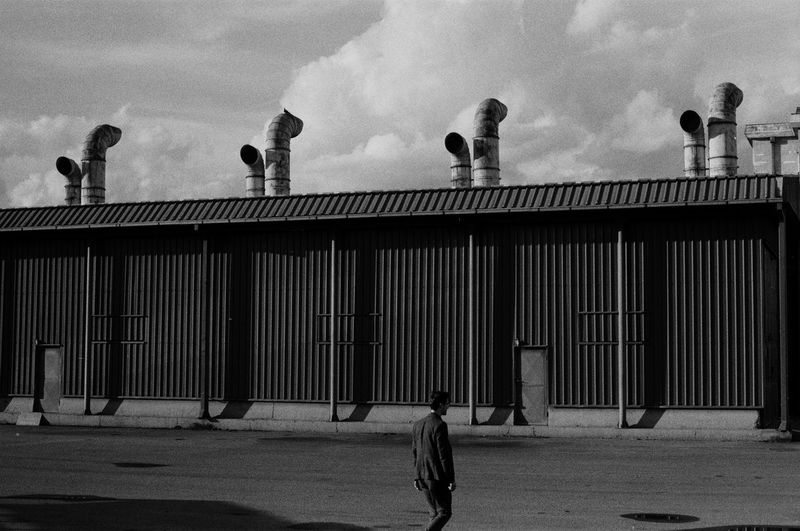 a man walking in an industrial zone Focus On Foreground Portrait Blackandwhite Outdoors Lifestyles Moody EyeEm Best Shots EyeEmNewHere EyeEm Selects Clothing Portrait Photography Film Film Photography 35mm Film Ilford Streetphotography Street Outdoor Photography Analog Industrial People Architecture Sky Built Structure Building Exterior Office Building