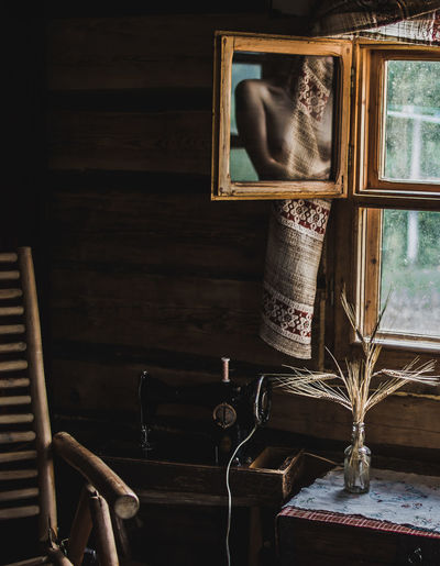 Shirtless woman reflecting on mirror by window at home