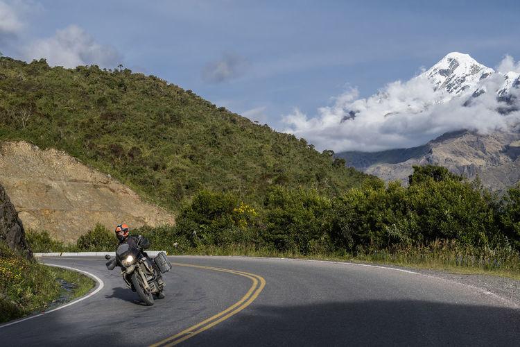 Man riding motorcycle on road against mountain range