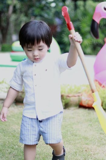 Cute Baby Boy Holding Shovel While Walking On Grassy Field