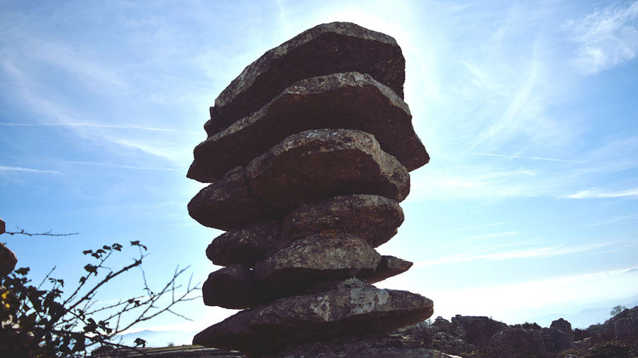 Low angle view of stone stack on rock against sky