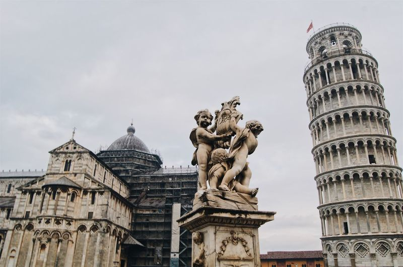 Low angle view of statue and leaning tower of pisa against sky