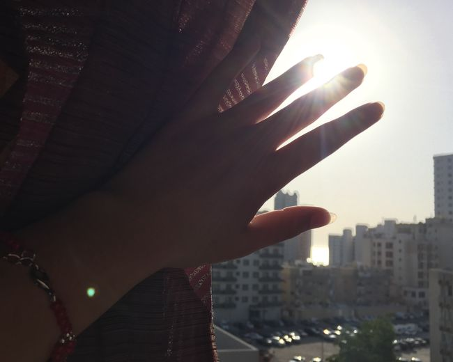 Close-up of woman hand against sky