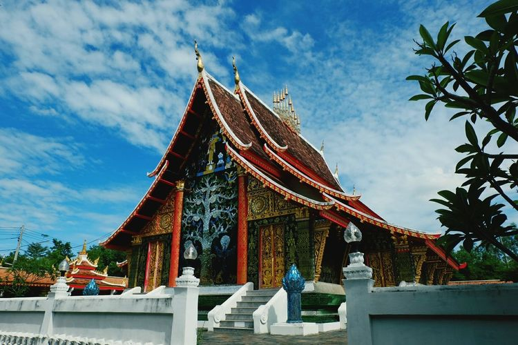 Low angle view of buddhist temple against cloudy blue sky on sunny day
