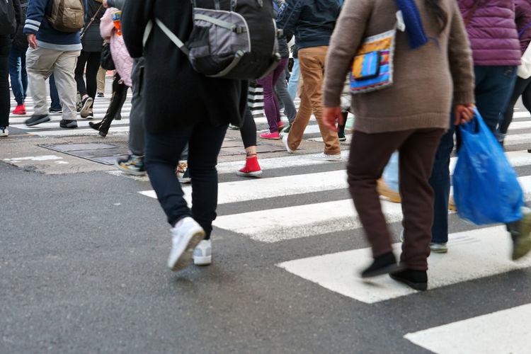 Low section of women walking on city street