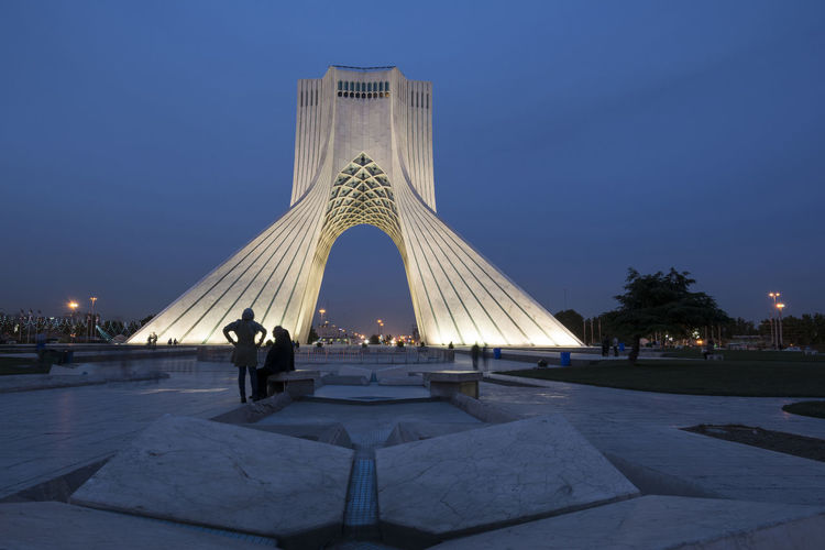 TEHRAN, IRAN - 7 May 2018 Azadi Tower at dusk time formerly known as the Shahyad Tower is a monument located at Azadi square and is an architectural landmark of Tehran Historical Building Architecture Azadi Tower In Tehran Blue Hour Landscape Building Exterior Built Structure City Clear Sky Dusk Group Of People History Illuminated Incidental People Landmark Memorial Men Nature Outdoors people and places Real People Sky The Past Tourism Travel Travel Destinations