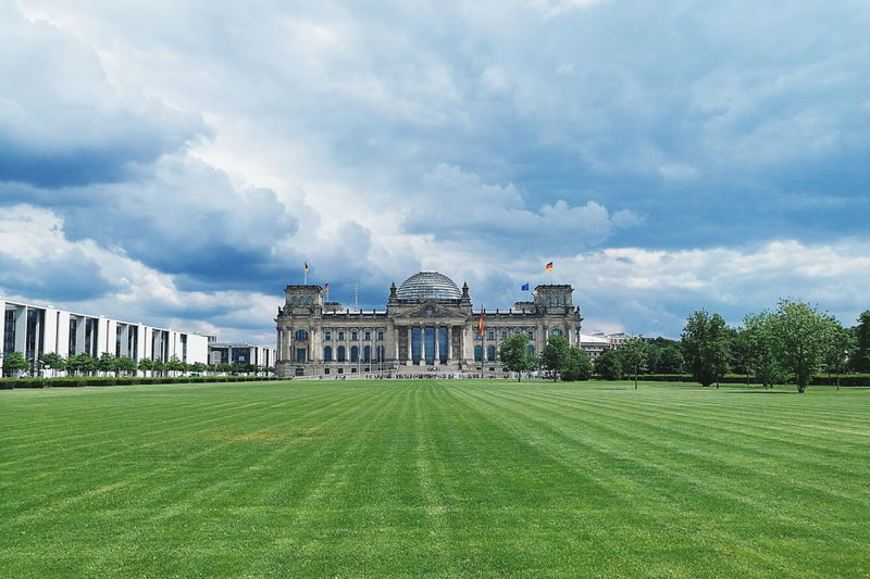 Reichstag building by platz der republik against cloudy sky