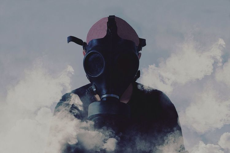 Man in gas mask amidst smoke