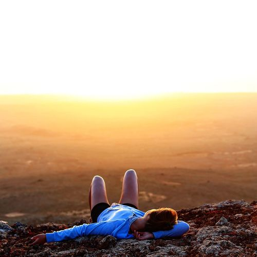 Woman sleeping on cliff against clear sky