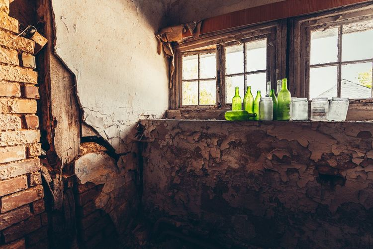View of weathered wall with some green bottles