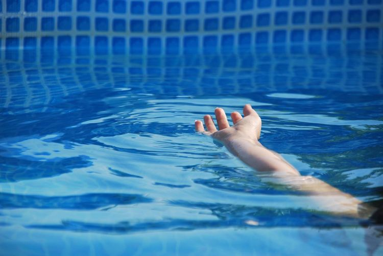 Cropped hand swimming in pool