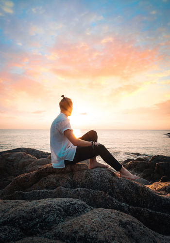 Sea Water Sky Sunset Real People Beauty In Nature Leisure Activity Lifestyles Scenics - Nature Solid Beach Rock Rock - Object Land Horizon Over Water Sitting Horizon Full Length Relaxation Couple - Relationship