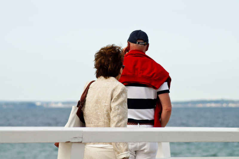 Man and woman standing at railing against sea