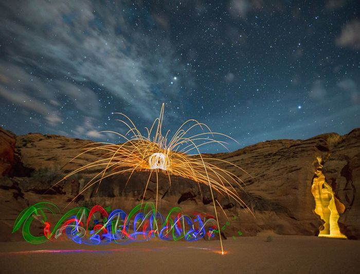 Light Paintings By Rock Formations Against Star Field At Night