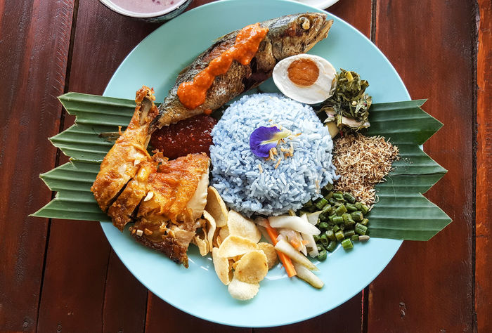 Nasi kerabu is a Malay rice dish, a type of nasi ulam, in which blue-coloured rice is eaten with dried fish, fried chicken, crackers, salted egg, pickles and other salads. ASIA Close-up Food Food And Drink Freshness Fried Healthy Eating High Angle View Indoors  Kelantan Kerabu Lunch Malay Malaysian Food Meal Meat Melaka No People Nyonyafood Plate Ready-to-eat Rice - Food Staple Serving Size Table Traditional