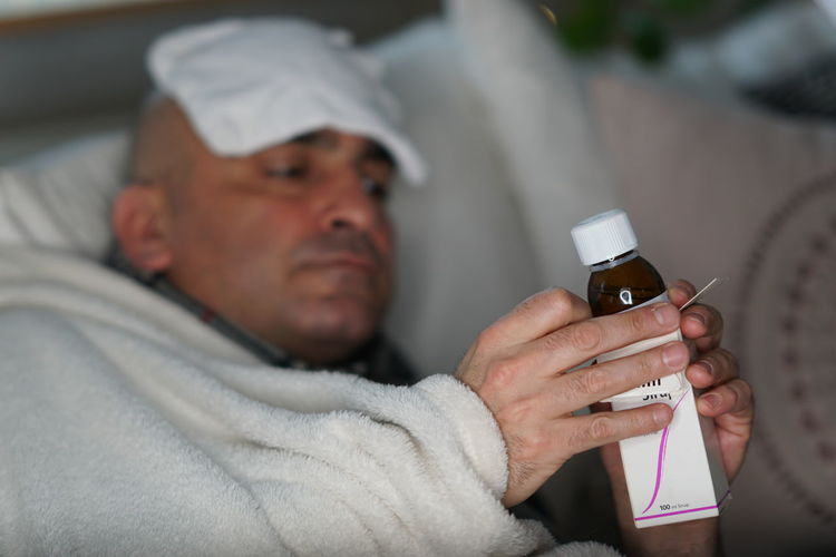 Close-up of man taking syrup