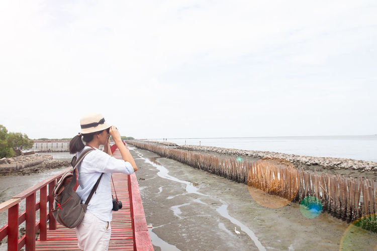 Woman backpacker taking photo, Lifestyle and Travel concept Advertising Happiness Happy Holiday Wellness Woman Advertisement Casual Clothing Clothing Copy Space Day Happiness ♡ Hat Leisure Activity Lifestyles Nature One Person Outdoors Real People Sea Seaside Sky Vacation Young Adult Young Women