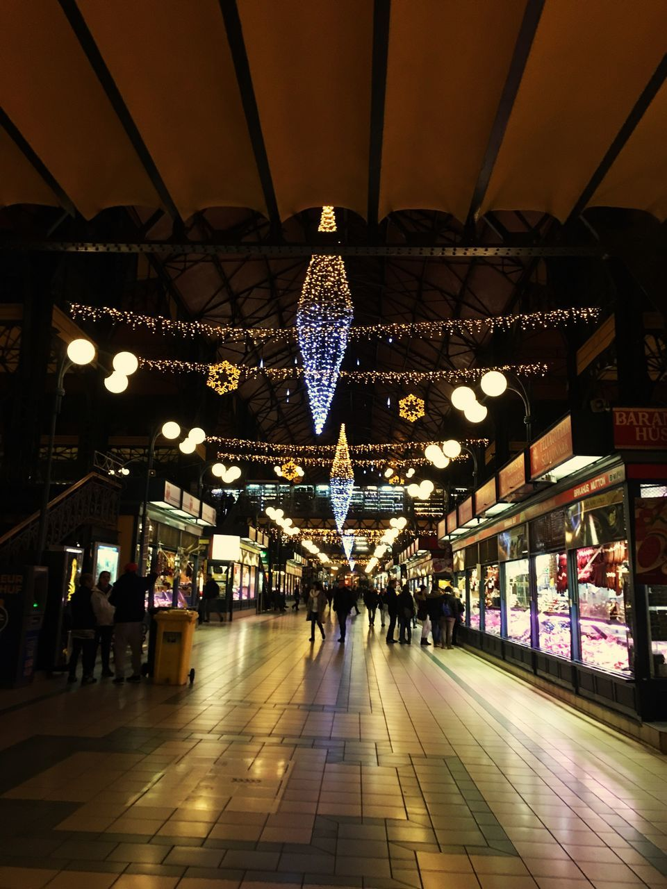 illuminated, lighting equipment, ceiling, indoors, real people, retail, large group of people, architecture, market, store, built structure, men, hanging, lifestyles, day, city, people