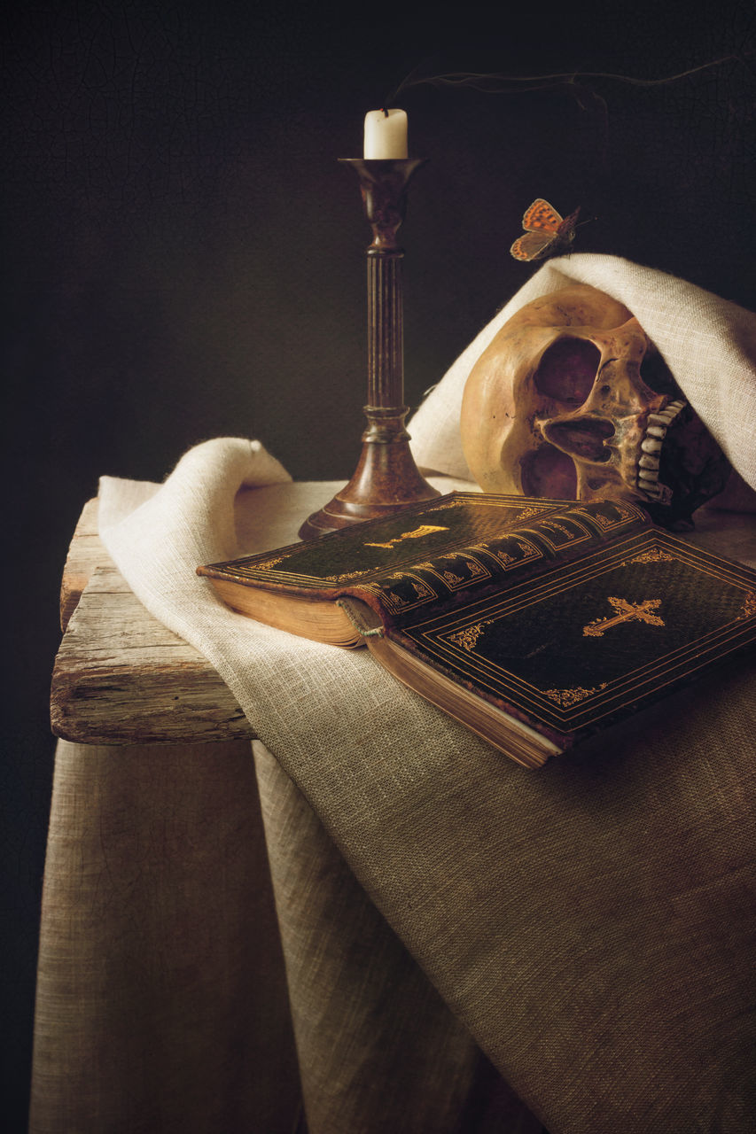 Close Up Of Bible By Candle And Skull Against Black Background