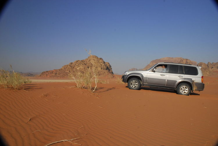 Car on desert land against clear blue sky