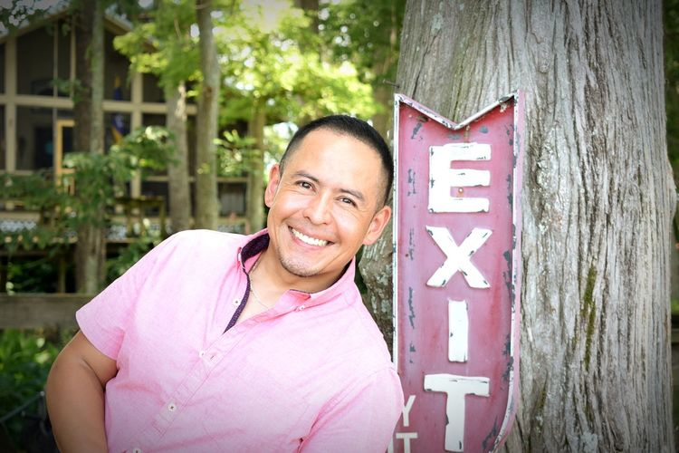 Portrait of smiling man leaning against exit sign on tree