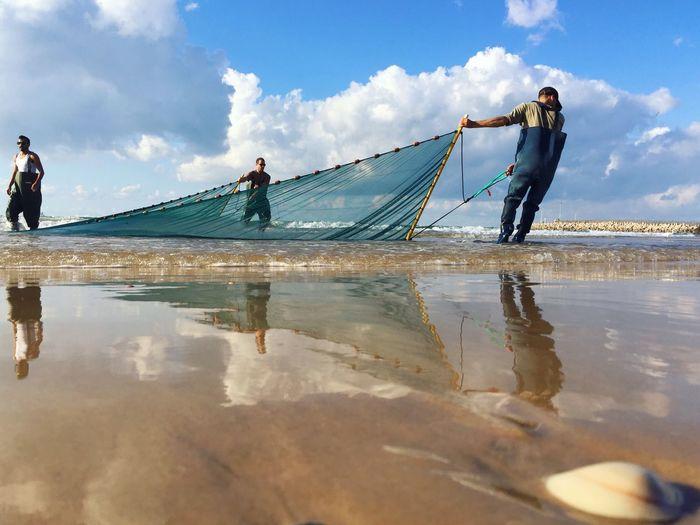 Man fishing in water against sky