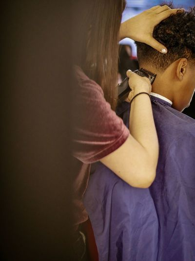 Woman shaving head of boy at barber shop