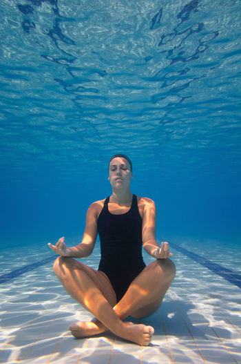 Female model meditating in pool