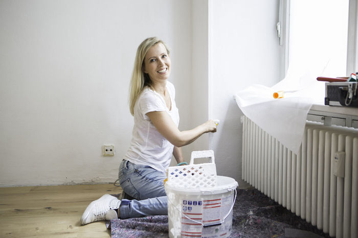 Blond haired lady smiling whilst doing some DIY Blond Hair Casual Clothing DIY Happiness Jeans Leisure Activity Lifestyles Painting Relax Renovations Young Lady
