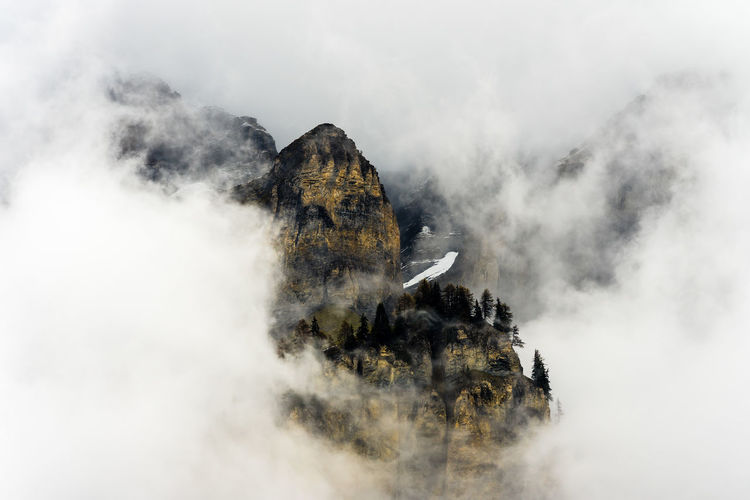 Scenic view of rock mountains during foggy weather