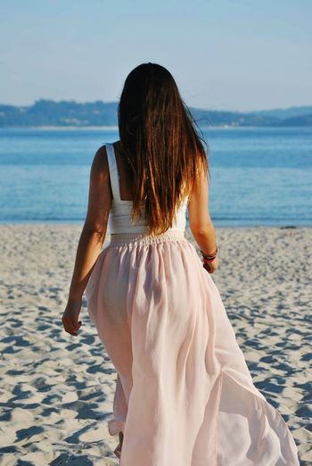Rear view of woman walking on sand at beach against sky
