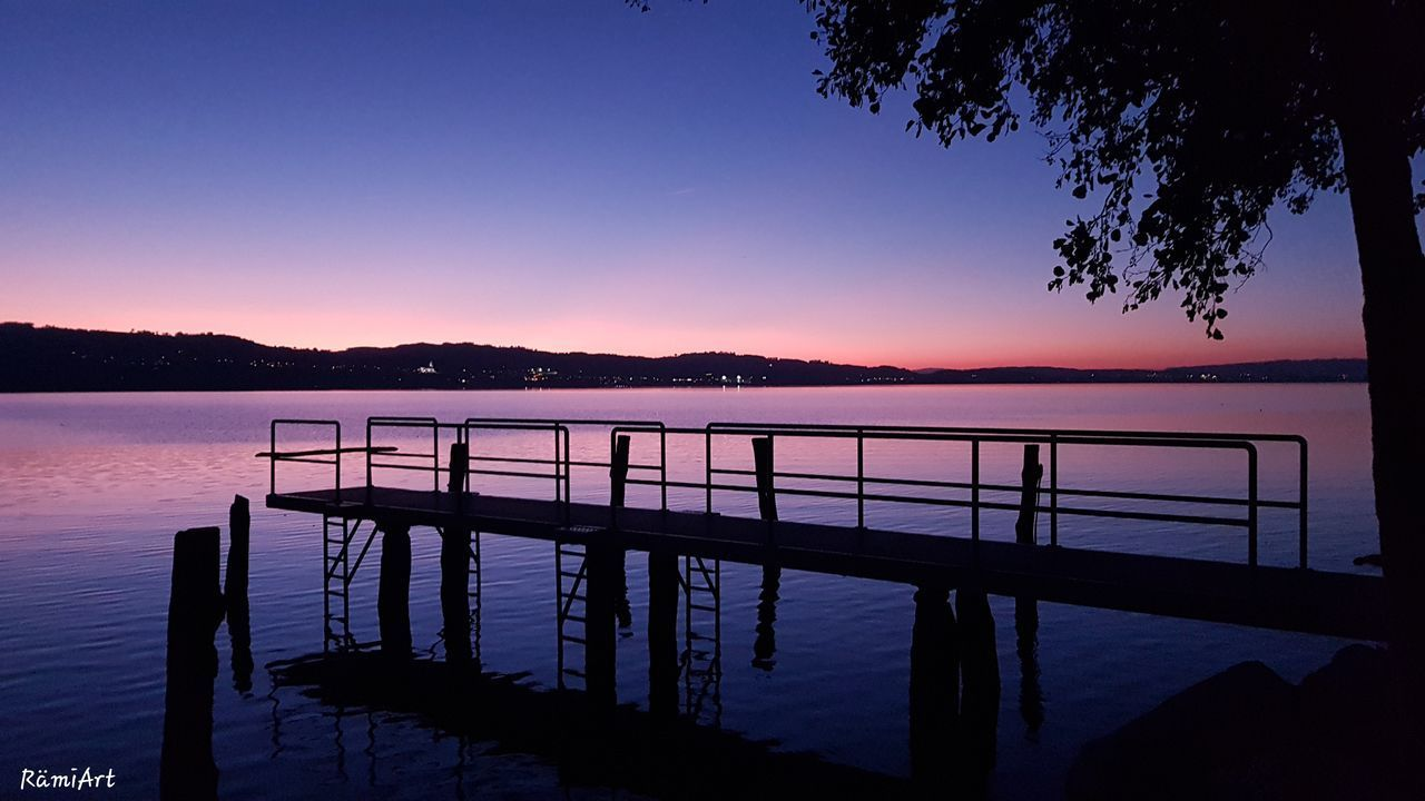 sky, water, sunset, beauty in nature, tranquil scene, tranquility, scenics - nature, silhouette, nature, idyllic, tree, railing, blue, non-urban scene, sea, no people, orange color, dusk, outdoors, purple