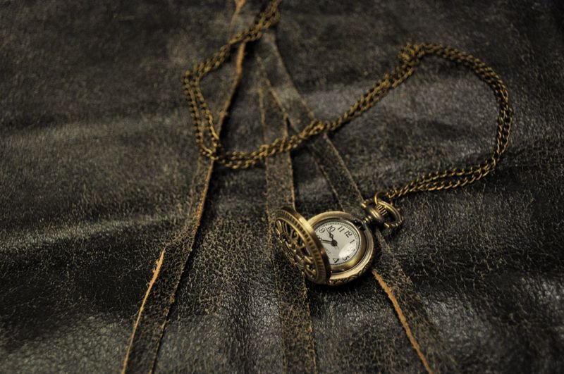 High angle view of pocket watch on textile