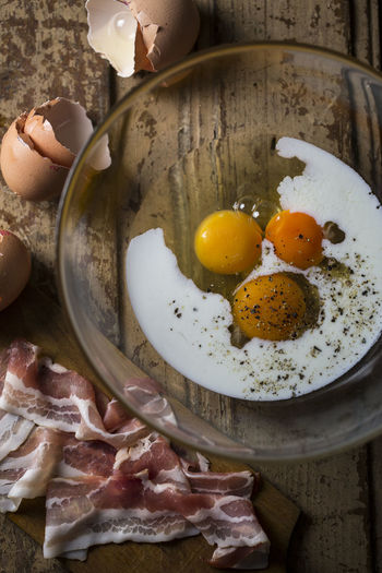 Directly above shot of egg yolk in bowl and bacon on wooden table